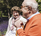 Senior couple sitting on bench in a park, talking - UUF14940