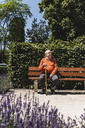 Senior man sitting on park bench, waiting - UUF14949