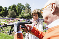 Senior couple playing with a drone in park - UUF14955