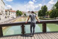 Italy, Veneto, Treviso, tourist looking on river - JUNF01137