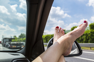 Italy, feet of woman leaning out of car window - JUNF01140