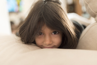 Portrait of little girl lying on sofa at home - JASF01906
