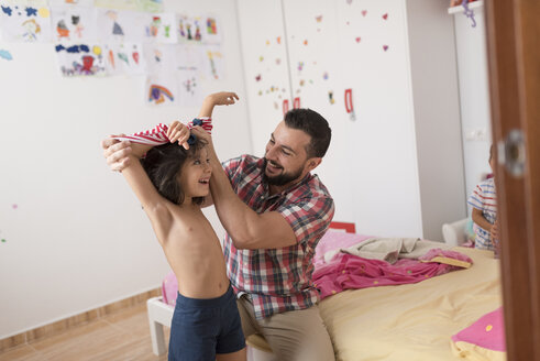 Happy father dressing daughter in home bedrom - JASF01912