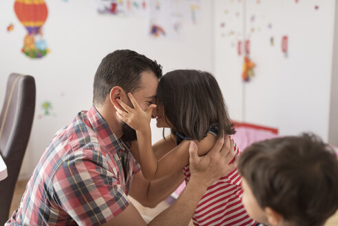 Happy father hugging daughter at home with son watching them - JASF01915