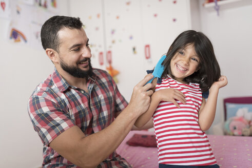 Happy father combing daughter at home - JASF01918