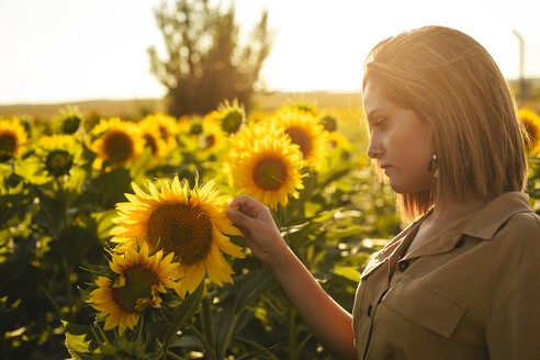 Portrait of a young woman in a sunflower field - ACPF00294