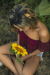 Young woman sitting in a field of sunflowers with a sunflower in her hand - ACPF00300