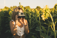 Young woman in a field of sunflowers taking pictures with an instant camera - ACPF00306