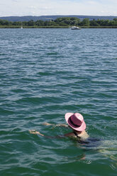 Woman wearing pink hat swimming in a lake - JTF01052