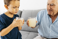Grandfather and grandson drinking lemonade at home - JRFF01808