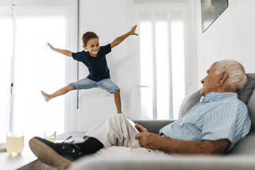 Grandfather sitting on the sofa with tablet watching his grandson jumping in the air - JRFF01814