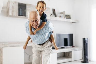 Portrait of grandfather giving his grandson a piggyback ride in the living room - JRFF01817