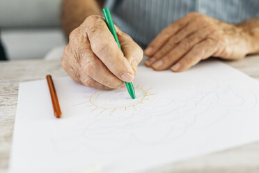 Senior man's hand drawing with green pencil, close-up - JRFF01823