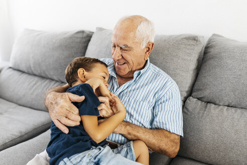 Grandson and grandfather laughing while tickling each other on the couch - JRFF01826