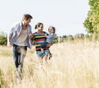 Happy family walking at the riverside on a beautiful summer day - UUF14965
