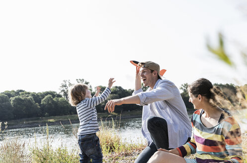 Happy family relaxing at the riverside, father and son playing with toy plane - UUF14989