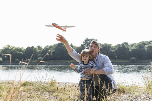 Father and son having fun at the riverside, playing with toy aeroplane - UUF14992