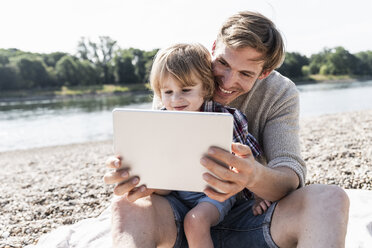 Father and son playing on digital tablet at the riverside - UUF15019