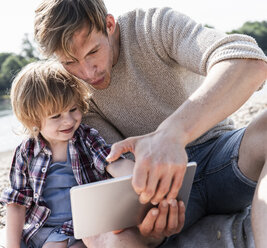 Father and son playing on digital tablet at the riverside - UUF15022