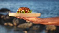 Woman's hand holding wooden plate with fishburger in front of the sea - RAMAF00036