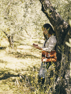Italy, woman leaning against olive tree using cell phone - RAMAF00072