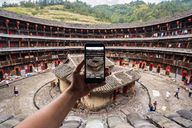 China, Fujian Province, hand taking cell phone picture of the inner courtyard of a tulou in a Hakka village - KKAF01494