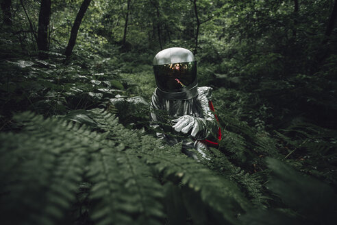 Spaceman exploring nature, examining plants in forest - VPIF00540