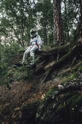 Spaceman exploring nature, sitting on tree roots - VPIF00549