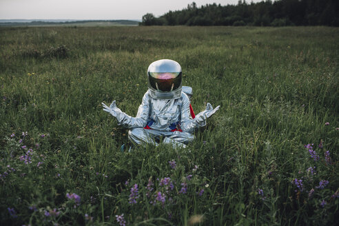 Spaceman exploring nature, sitting in meadow, meditating - VPIF00573