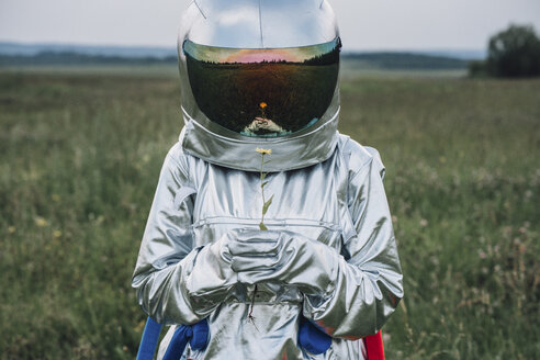 Spaceman holding flower, watching it grow - VPIF00591