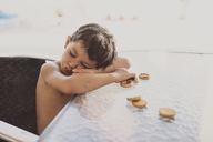 Portrait of little boy falling asleep while eating chocolate cookies - JASF01924