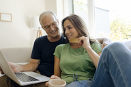 Smiling mature couple sitting on couch at home shopping online with laptop - KNSF04598