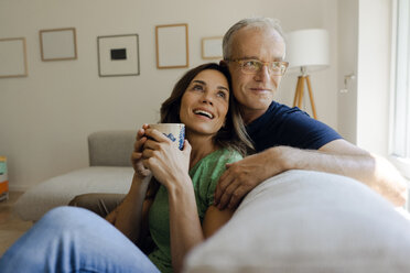 Happy mature couple sitting on couch at home - KNSF04601