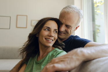 Smiling mature couple sitting on couch at home - KNSF04604