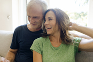 Happy mature couple sitting on couch at home - KNSF04607