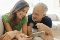 Smiling mature couple lying on couch at home sharing tablet - KNSF04616