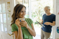 Mature couple at home with woman drinking coffee and man reading newspaper - KNSF04619