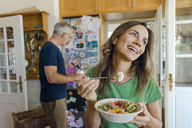 Happy mature woman at home eating a salad with man in background - KNSF04622
