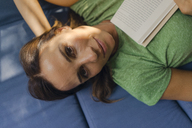 Portrait of smiling mature woman lying on couch at home with book - KNSF04625