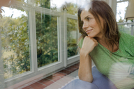 Smiling mature woman on couch at home looking out of window - KNSF04631