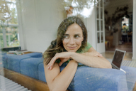 Smiling mature woman on couch at home looking sideways - KNSF04634