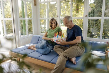 Happy mature couple sitting on couch at home with fake birthday cake - KNSF04637