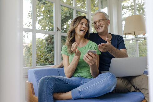Happy mature couple sitting on couch at home with cell phone and laptop - KNSF04643