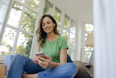Smilong mature woman sitting on couch at home using cell phone with man in background - KNSF04646