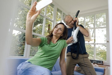 Mature woman taking a selfie at home with man playing toy electric guitar - KNSF04649