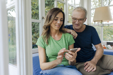 Smiling mature couple sitting on couch at home sharing cell phone - KNSF04652