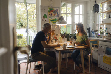 Mature couple sitting at kitchen table at home - KNSF04658