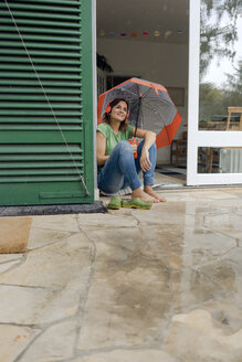 Smiling mature woman sitting on terrace in rain under umbrella listening to music with headphones - KNSF04664