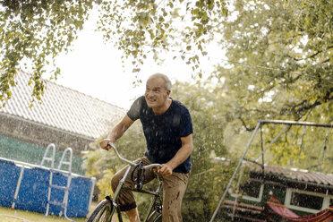 Happy mature man riding bicycle in summer rain in garden - KNSF04667