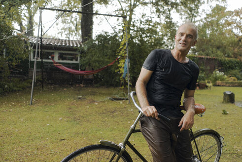 Portrait of mature man with bicycle in summer rain in garden - KNSF04673